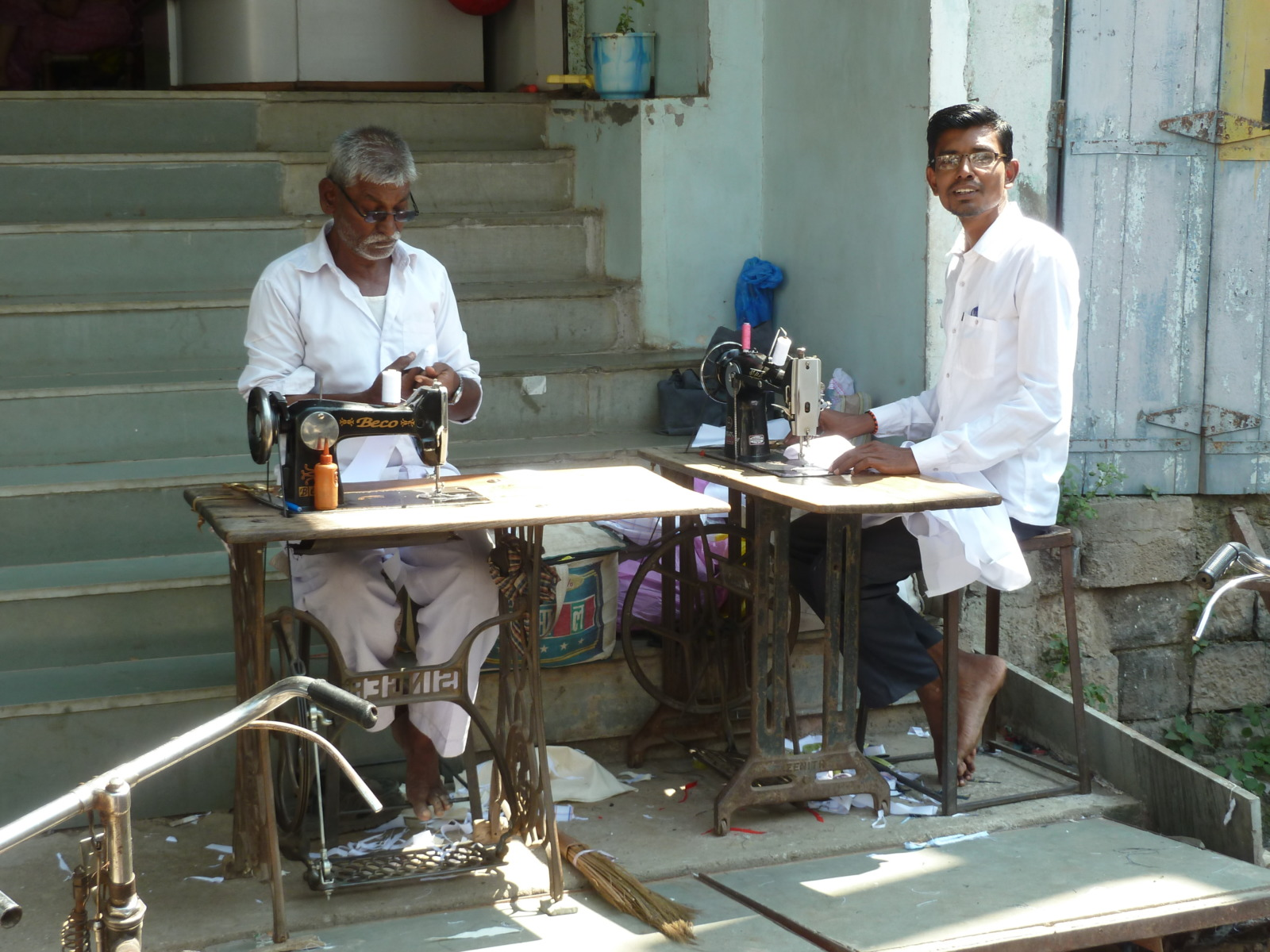 Two men sewing on the street